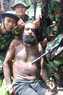 Indonesian soliders pose for a 'trophy photo' after killing West Papuan tribal elder Yustinus Murib