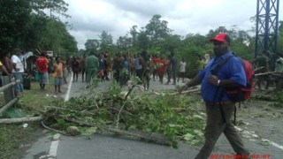 Papuans block the road following the shooting of Andreas