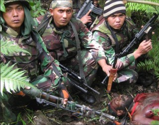 Indonesian soldiers pose for a trophy photo after murdering a tribal leader in the West Papua highlands
