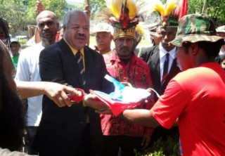 Powes Parkop receives the West Papuan flag alongside Benny Wenda shortly before raising it in in the capital of PNG