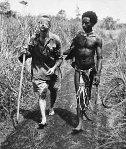 "Christmas Day, 1942. An Australian soldier, George ""Dick"" Whittington, is aided by Papuan orderly Raphael Oimbari, at the Battle of Buna-Gona. Picture by George Silk"