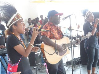 Sir George Telek performs on stage alongside West Papuan students