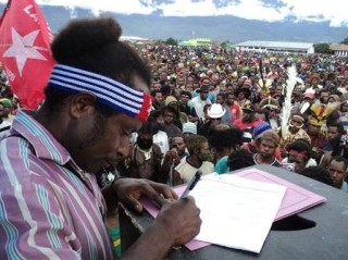 West Papuans signing documents at a rally