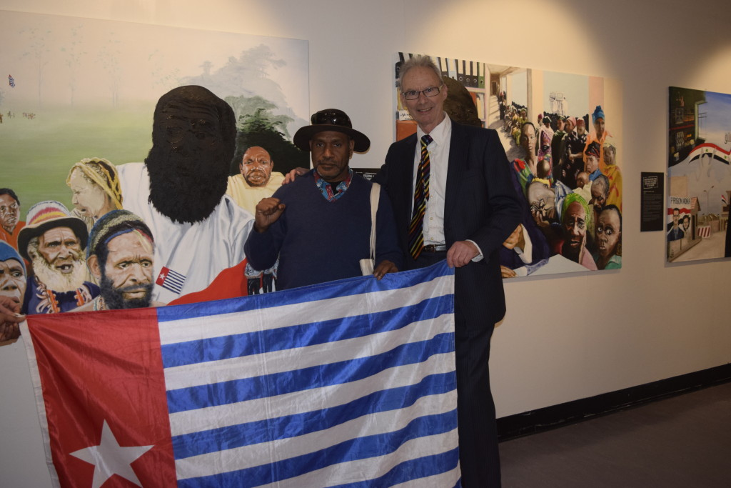 West Papuan Independence Leader, Benny Wenda meeting UK artist Paul Piercy in front of Paul's painting of West Papuan political prisoner Filep Karma