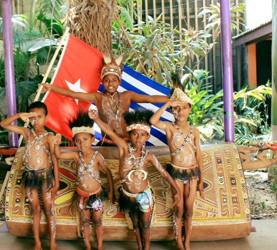 West Papuan boys in traditional dress, saluting in front of their national flag and a garamut drum
